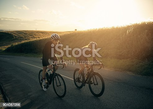 Shot of two cyclists out cycling on a country road