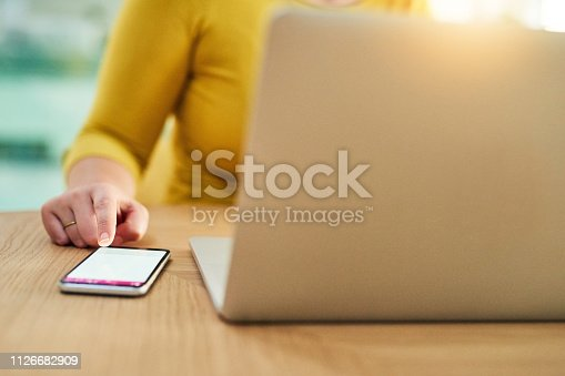 Cropped shot of an unidentifiable businesswoman using a mobile phone and laptop at work
