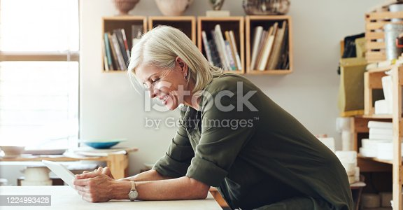 Shot of a mature woman using a digital tablet while working in a pottery studio