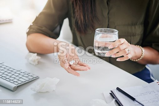 Closeup shot of an unrecognisable businesswoman holding a glass of water and medication in an office