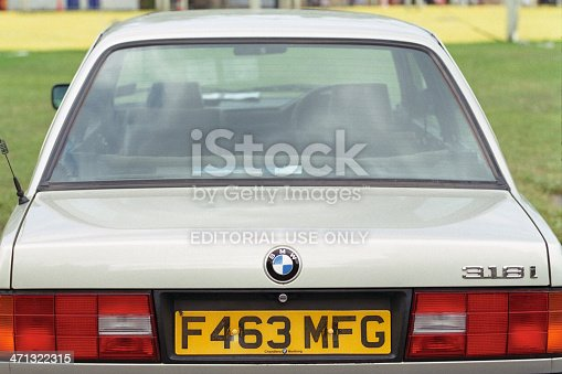 Durham, England - June 10, 2011: Rear of an old BMW 318i (codenamed E30), photographed in Palace Green. The two colours of the grass is explained by a recently dismantled exhibition tent. On the registration plate, the name of the seller