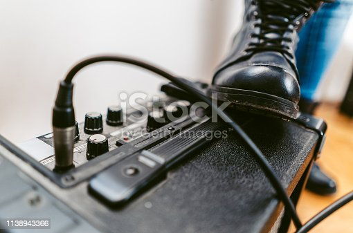 Close up picture of a black boot stepping on amplifier