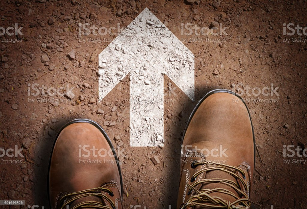 Boot on the trail with Direction Arrow stock photo