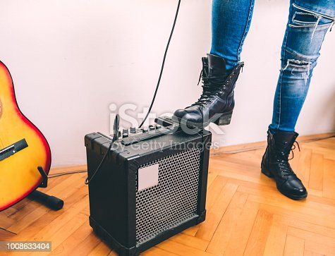 Young girl's leg stepping onto a guitar amplifier, dressed in jeans and black boots.