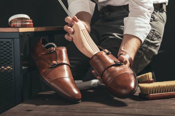 skoputsare förbereder skor för rengöring i sin verkstad - remmar godis bildbanksfoton och bilder