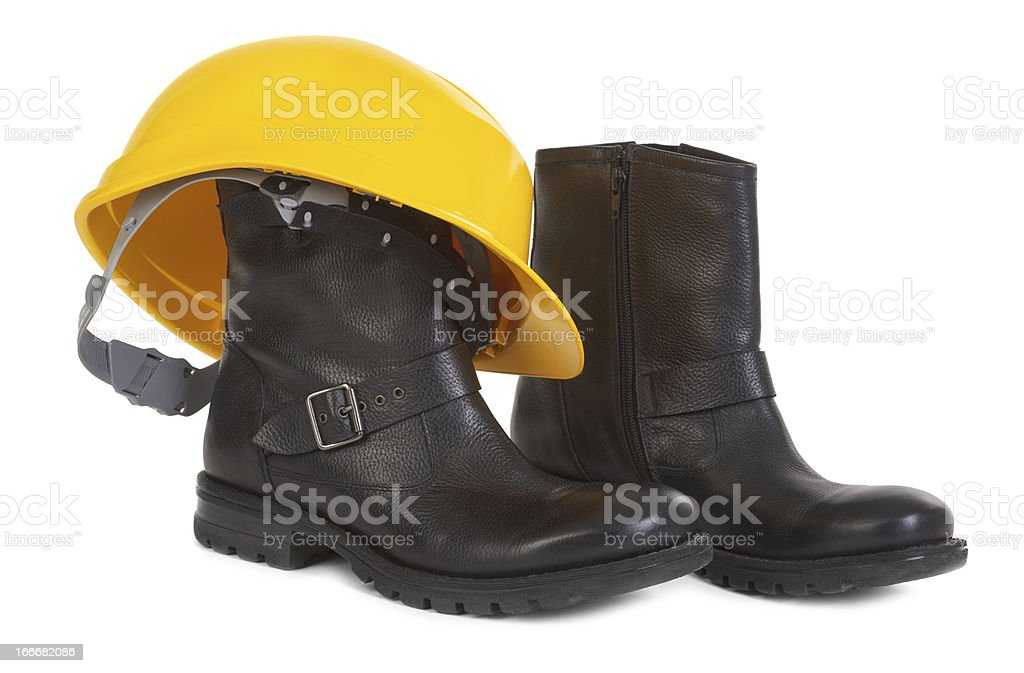 Boots and yellow hard hat over white background royalty-free stock photo