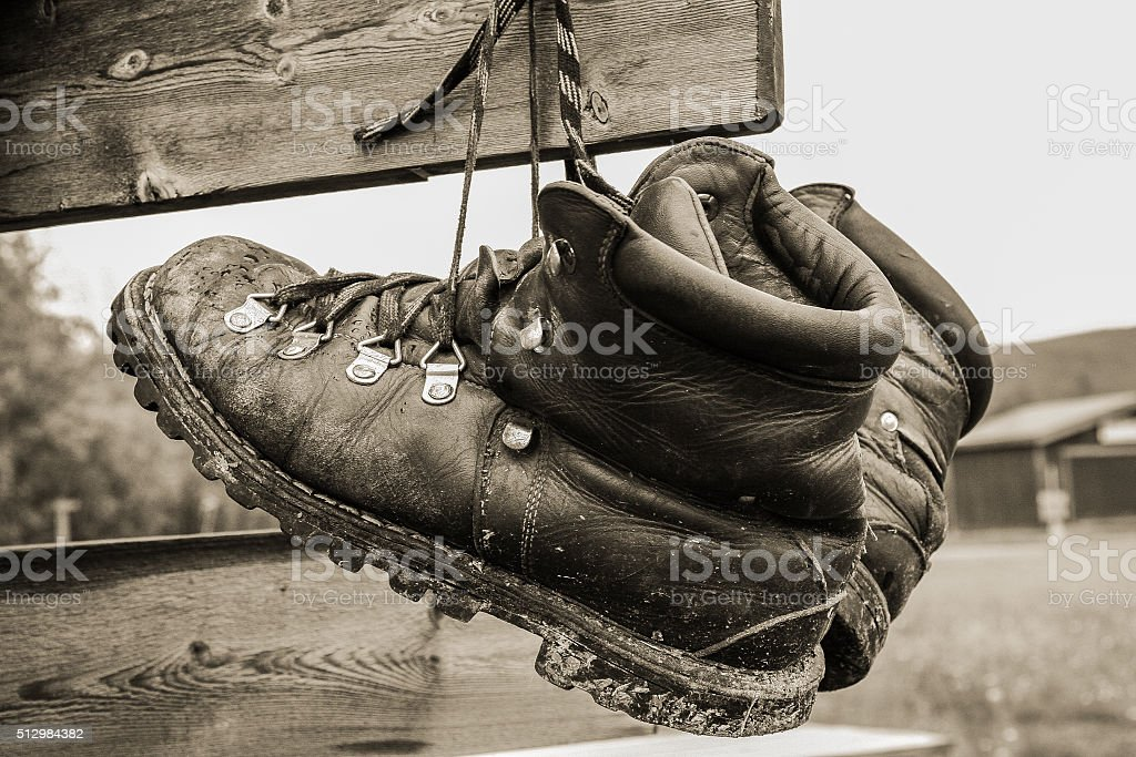 boots drying hanging on a sign post stock photo