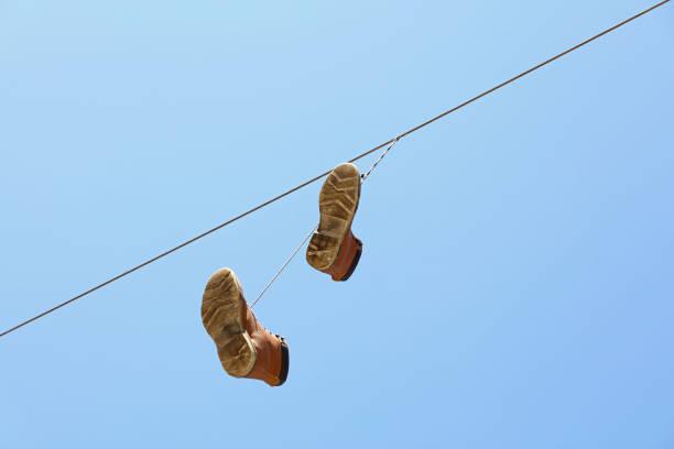 stiefel, hängen an einem draht über klar blauen himmel - kabelschuhe stock-fotos und bilder