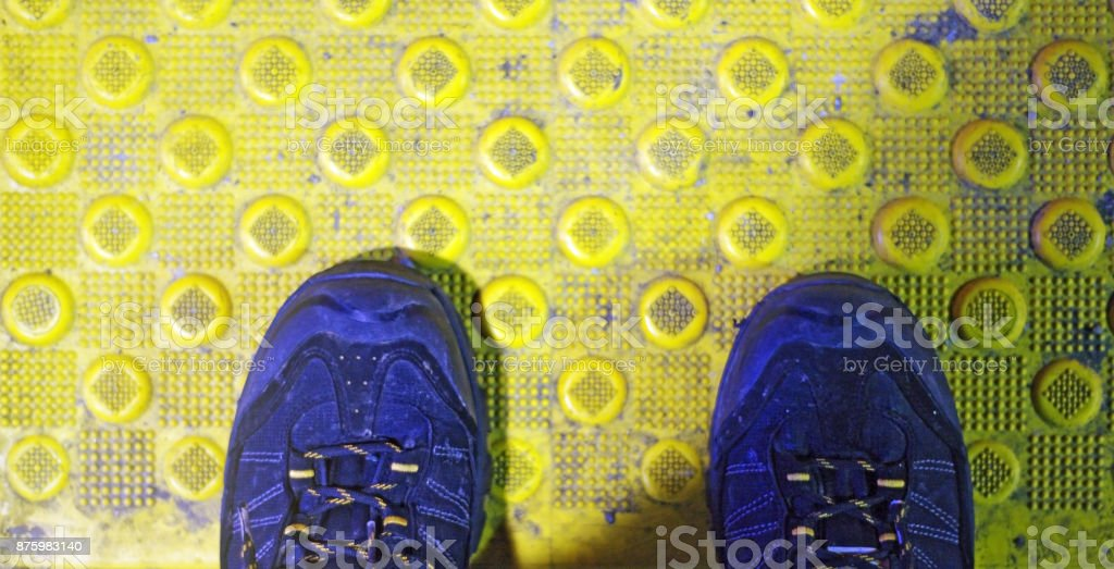 Boots on yellow transit line at night stock photo