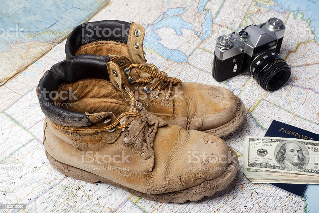 Boots passport US dollars and camera on map background royalty-free stock photo