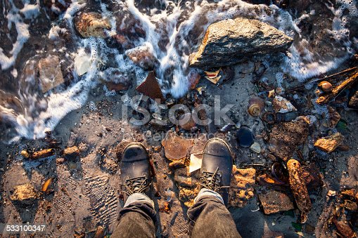 Boots of a person standing on the rocky shore of a beach littered with trash