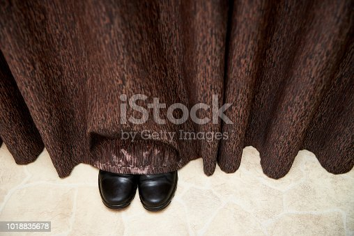 Boots stick out from under the curtains