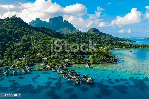 Bora Bora aerial drone video of travel vacation paradise with overwater bungalows luxury resort, coral reef lagoon ocean beach. Mount Otemanu, Bora Bora, French Polynesia, Tahiti, South Pacific Ocean