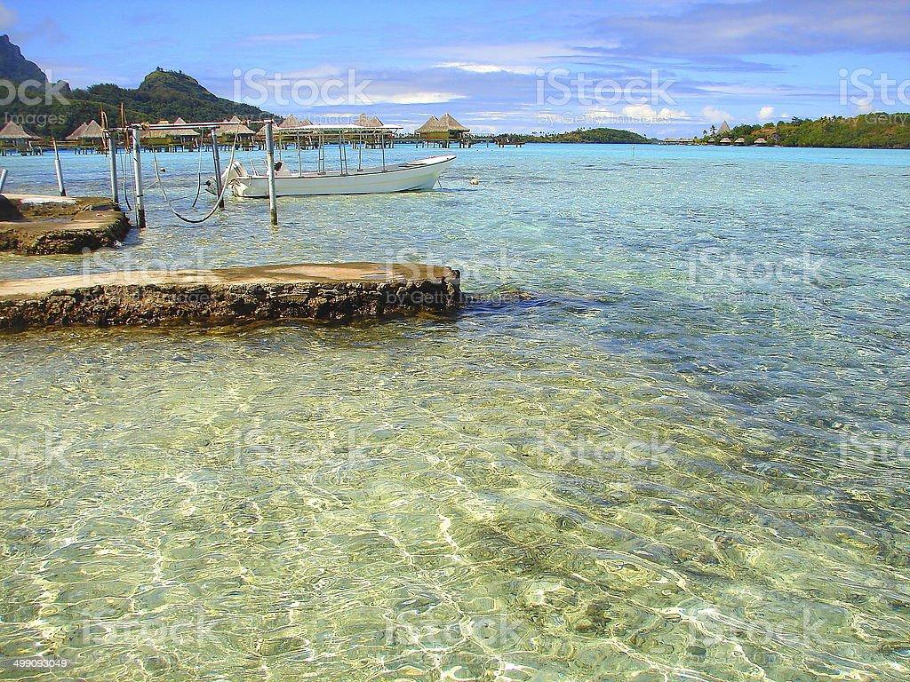 Bora Bora Bungalows and fishing boat pier on turquoise beach, Polynesia royalty-free stock photo