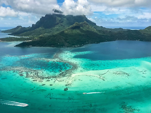 Bora Bora Island Aerial View French Polynesia Aerial view of Bora Bora island over beautiful turquoise lagoon with speedboats to volcanic Mount Otemanu. Bora Bora, Society Islands, French Polynesia. volcanic landscape stock pictures, royalty-free photos & images