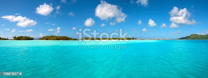 Wide view the beautiful lagoon and small islands on the Bora Bora reef. French Polynesia, South Pacific Ocean.