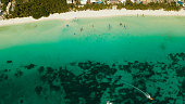 Tropical white sand beach in a lagoon with turquoise water on Boracay Island, Philippines., aerial view. Seascape with beach on tropical island. Summer and travel vacation concept.