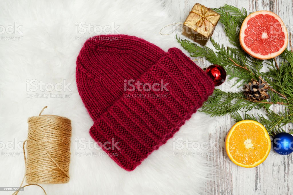 Bordeaux hat, spruce branch, Christmas tree decorations and citrus. New Year's concept. stock photo