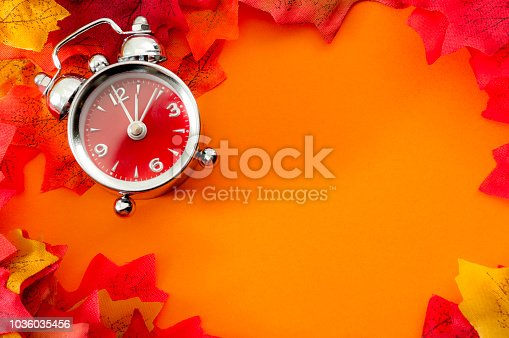 istock border around orange background with clock and leafs with copyspace 1036035456