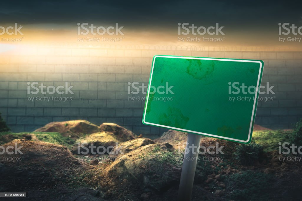 border concept with blank sign in front of a high wall and dramatic...