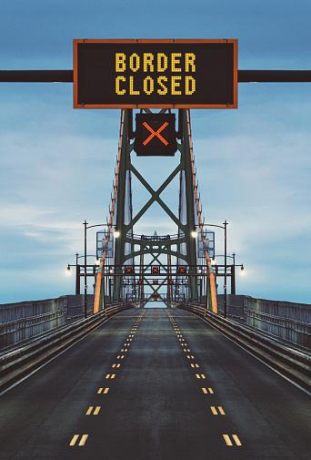Border closed displayed on overhead bridge sign. Composite image.