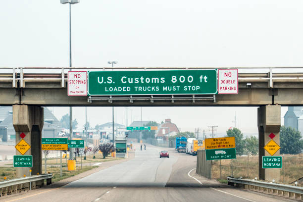 Border crossing Signs indicate that drivers are approaching the U.S. Customs area in Sweet Grass, Montana near the Canadian border. geographical border stock pictures, royalty-free photos & images