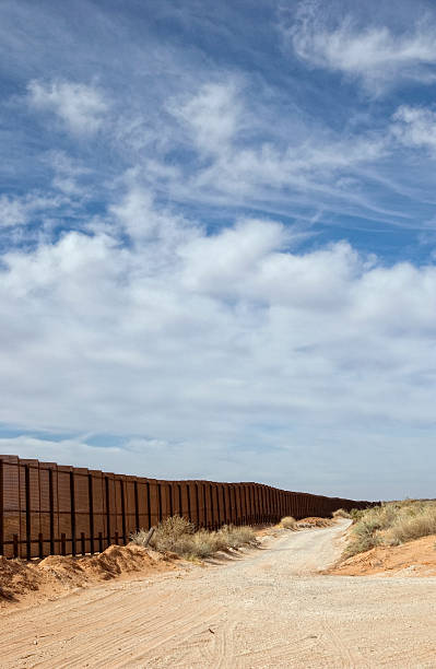 Border Fence Along Dirt Road The border fence along a dirt road in the desert separating Mexico and New Mexico. Near Juarez and El Paso.  international border barrier stock pictures, royalty-free photos & images