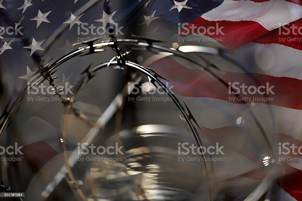 USA Border fence barb razor wire Flag Immigration Concept stock photo