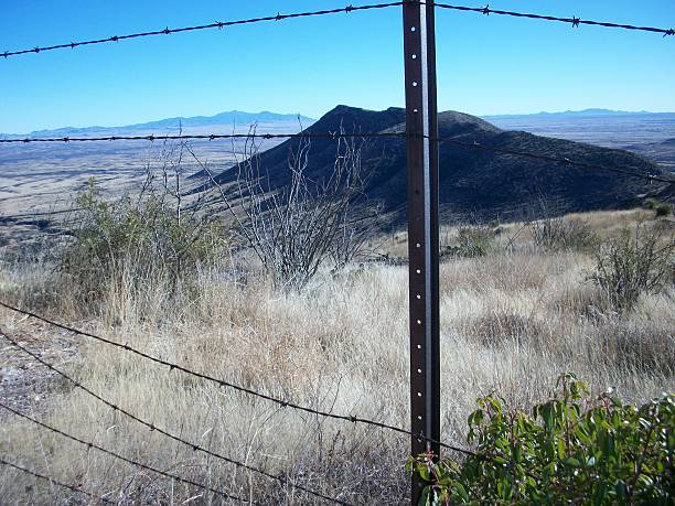 Border Fence in Southeast Arizona The boarder fence, through much of Southern Arizona border looks like this. Just an old rusty barbed wire fence with gaping holes is supposed to stop people and contraband from illegally crossing the US border. drug cartel stock pictures, royalty-free photos & images