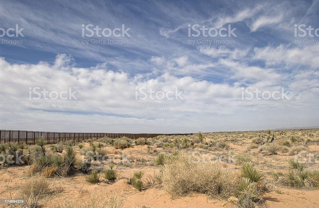 Border Fence in the Desert  Barricade Stock Photo