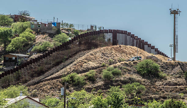 Border fence separating Mexico and the United States Border fence looking from Nogales Arizona into Nogales in Sonora Mexico international border barrier stock pictures, royalty-free photos & images