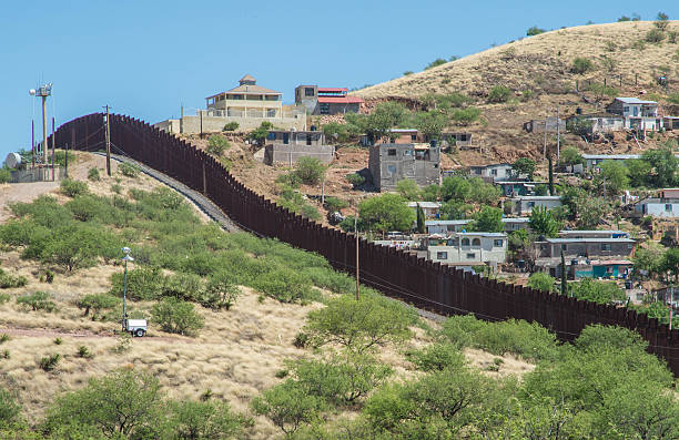 Border fence separating Mexico and the United States Border fence looking from Nogales Arizona into Nogales in Sonora Mexico border patrol stock pictures, royalty-free photos & images