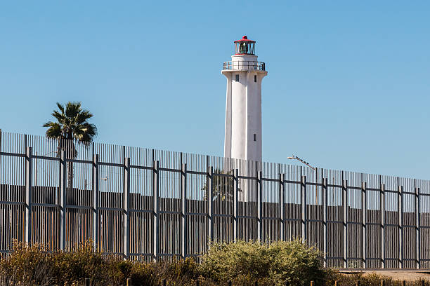 Border Fence Separating San Diego and Tijuana with Lighthouse stock photo