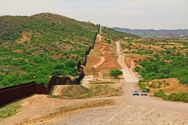 Border Fence Separating the US from Mexico Near Nogales, Arizona Border Fence beside a road near Nogales, Arizona separating the United States from Mexico with border patrol vehicle. geographical border stock pictures, royalty-free photos & images