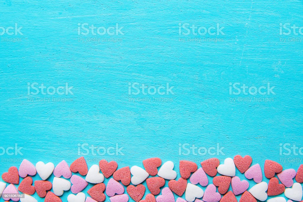 Border Frame from Colorful Sugar Sprinkles Candies Scattered on Light Blue Background. Valentine Romantic Birthday Charity Mother's Day Concept. Greeting Card Poster Template Copy Space stock photo