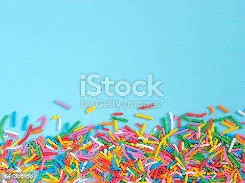 istock Border frame of colorful sprinkles on blue background 647358186
