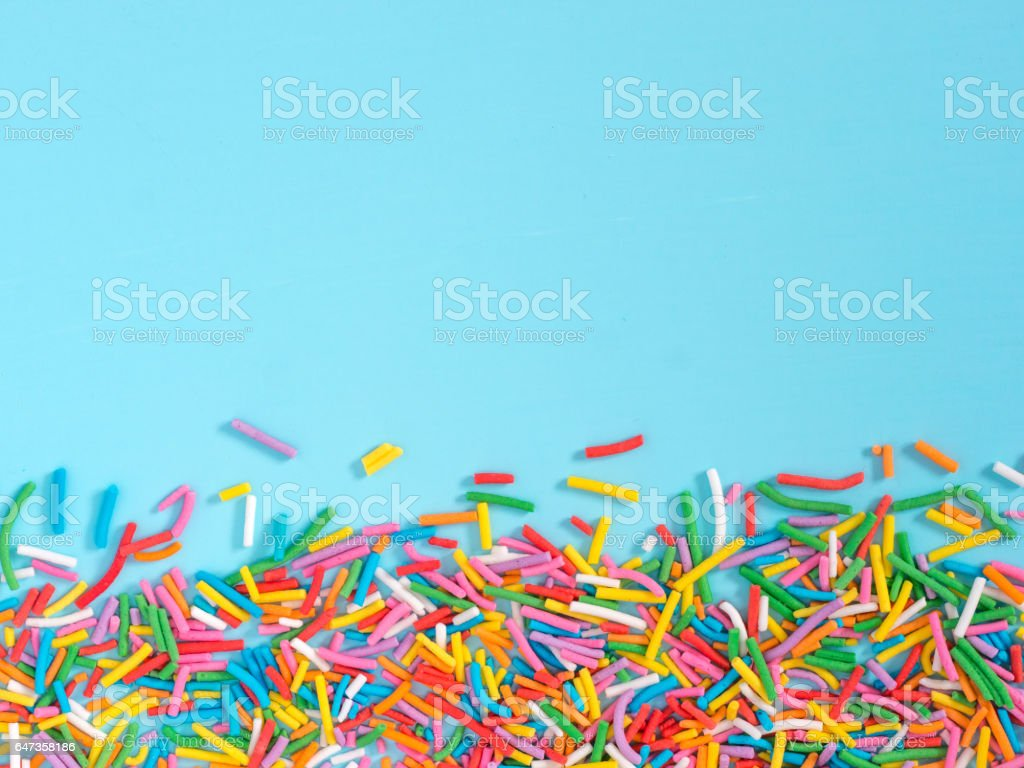 Border frame of colorful sprinkles on blue background stock photo
