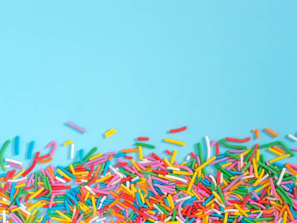 Border frame of colorful sprinkles on blue background stock photo