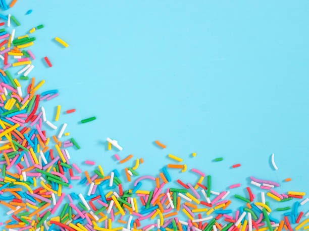 border frame of colorful sprinkles on blue background - posypka zdjęcia i obrazy z banku zdjęć