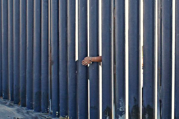 Border Hands Hands reach through the border wall of Mexico. international border barrier stock pictures, royalty-free photos & images