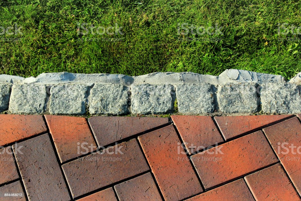 Border kerb between green grass lawn and tiled sidewalk in a park stock photo