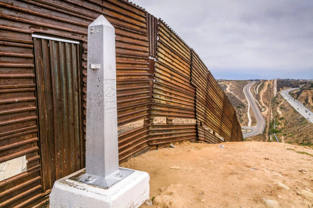 USA/Mexico Border - The Wall Tijuana, Mexico, Jul 07 - A border monolith in the Mexican side of the steel wall on the border between the United States and Mexico, on the Pacific coast of Playas de Tijuana. In the background the border area of the Canyon del Muerto recognition. On the right the Mexican territory, on the left the US territory. foreign affairs stock pictures, royalty-free photos & images