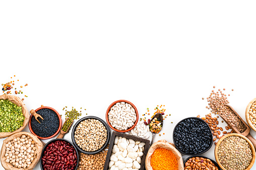 Food Backgrounds: large variety of dried beans, legumes and cereals arranged at the bottom of a white background making a frame and leaving useful copy space for text and/or logo. The composition includes green, yellow and brown lentils, chick-peas, black beans, Pinto beans, Kidney beans, fava beans, mung beans, white beans and soy beans among others. High resolution 42Mp studio digital capture taken with SONY A7rII and Zeiss Batis 40mm F2.0 CF lens