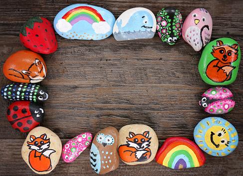istock Border of Colorful Cartoon Hand Painted Animal Rocks on Wood Background 1049472180