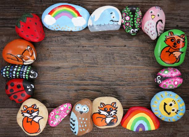 Border of Colorful Cartoon Hand Painted Animal Rocks on Wood Background stock photo