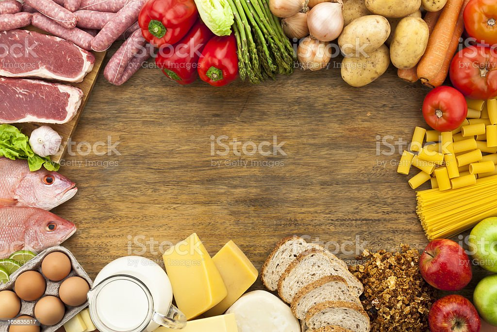 Border of different types of food on wooden table stock photo