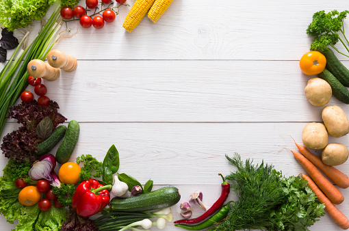Border of fresh vegetables on white wood background with copy space
