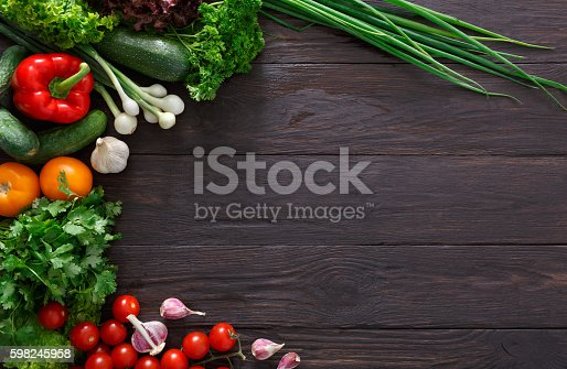 istock Border of fresh vegetables on wooden background with copy space 598245958