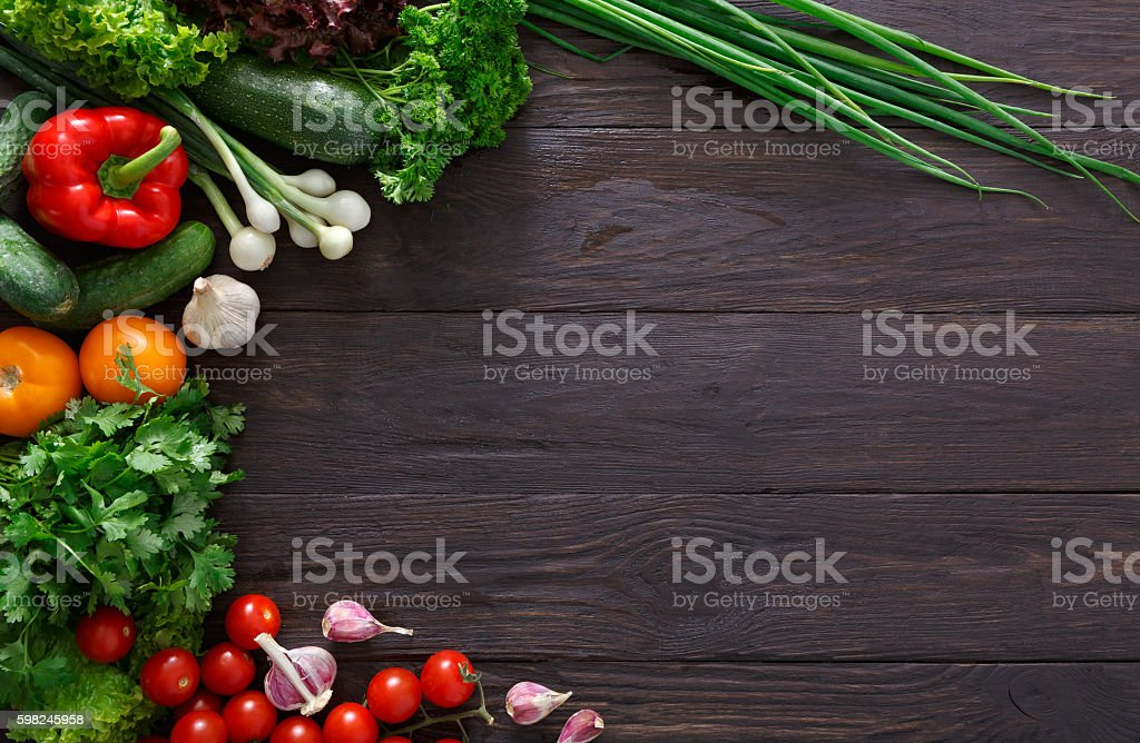 Border of fresh vegetables on wooden background with copy space stock photo