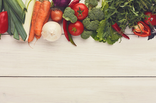istock Border of fresh vegetables on wooden background with copy space 909517902